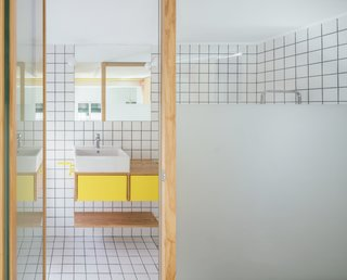 The bathroom has two glass walls with frosted and transparent glass to allow light to filter in from the windowed area. Colored grout and yellow drawers and hardware bring bright colors into the space.