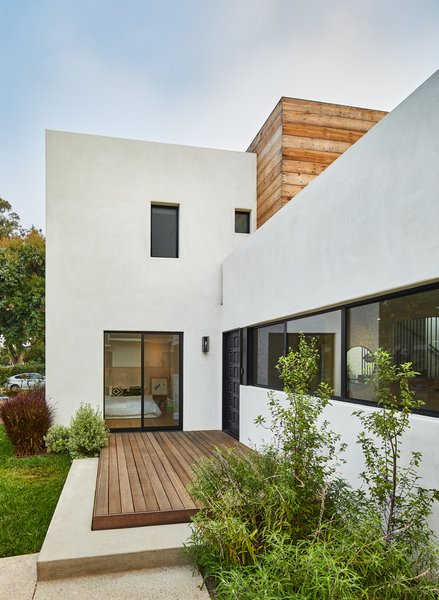 The multiple planes of the facade create a complex form, allowing part of the second floor to hide behind the white plaster cement mass at the front of the home.