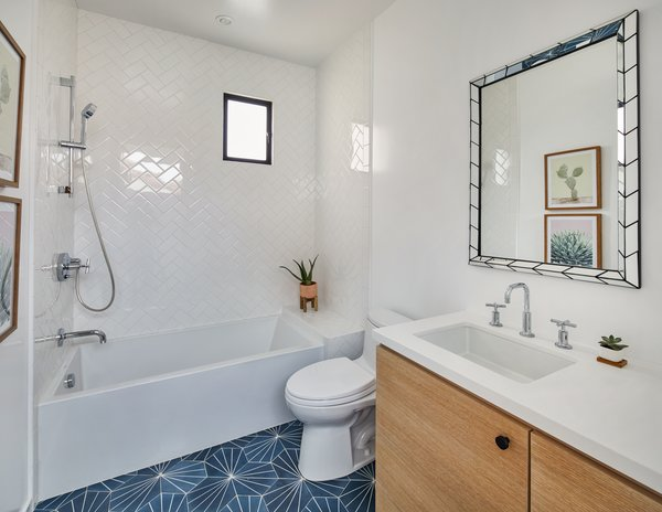 One of the bathrooms on the second floor contrasts crisp white tile on the walls with geometric blue tile on the floor.