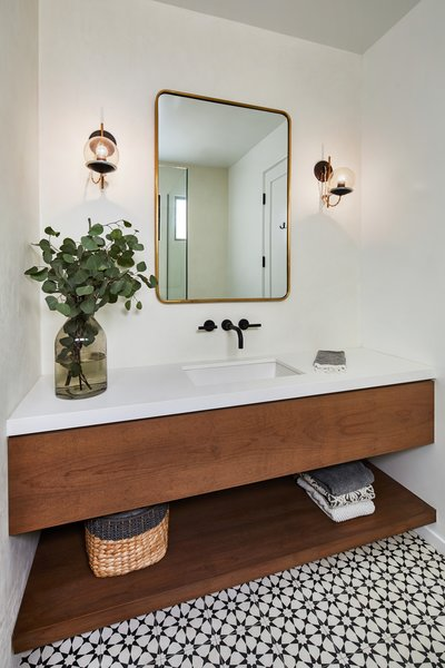 A white and wood bathroom is complemented by patterned geometric tile and a simple metal mirror.