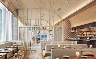 The interiors of ATX Cocina in Austin feature lots of wood, neutral tones with pops of color, and a vaulted ceiling to create a sense of enclosure.