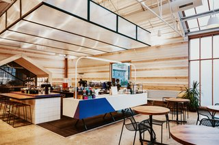 The light-filled, wood-clad flagship of Greater Goods Roasting in Austin features various types of seating including wood tables with black metal mesh chairs, wood benches, high stools, and plush armchairs and sofas.