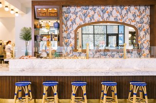 Textured wood walls and bar, bold textiles, and moody paint colors create a modern French vibe in Austin's Le Politique restaurant.
