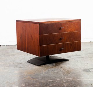Known for his design-forward but unpretentious work, furniture designer Milo Baughman created this walnut veneer bedside table with a sculptural metal base, so that it almost appears to hover over the ground.