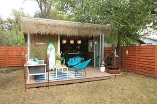 Made from a customized DIY version of an off-the-shelf shed from Tuff Shed, this she shed now houses a bar and opens onto a deck with an outdoor oven and furniture and seating for friends and family.
