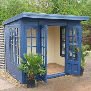 This backyard shed, painted a soulful blue and full of light from windows on three sides, is a great example of a kit she shed. It's the perfect place to escape to for some yoga, art, or reading.