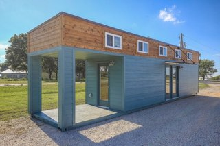 At 320 square feet, the Front Porch Living model by Custom Container Living consists of one shipping container with a covered front porch that extends from the end of the home. The home's exterior is clad in wood siding. Pricing for the home starts at $56,400.