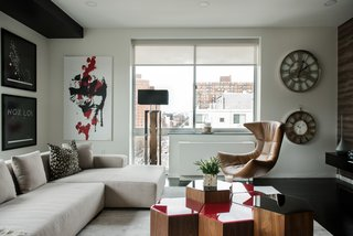 In this apartment, Kesha Franklin of Halden Interiors employs a palette of off-whites paired with a dark floor; moments of red in both the artwork and accent furniture enliven the space.