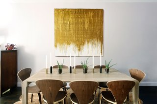 At an apartment in Brookyln, AphroChic designers Jeanine Hays and Bryan Mason played with different tones of wood and metal in the dining area to achieve a space that is both modern and elegant; the light gray color of the walls keeps the space from feeling too sterile, and provides a warm backdrop for the gold-and-white artwork.