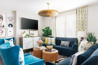 This living room designed by interior designer Veronica Solomon incorporates multiple patterns and bold colors that manage to not overpower each other because of the room's high ceilings, light-colored walls, and simple but statement light fixture at the center of the space.