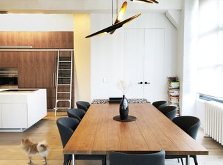 In a condo renovation by architect Samantha Josaphat of Studio 397 Architecture, a kitchen with a generous island opens onto a dining area. The kitchen takes full advantage of the apartment's high ceilings with upper cabinets accessible via a ladder, while the dining area has a sculptural pendant fixture that creates a sense of space and ambiance.