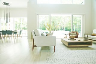 At a five-bedroom pied-a-terre in the Hamptons, Ishka Designs employs a lighter, more monochromatic palette for a repeat client; the design emphasizes the plentiful daylight the living and dining areas receive from double-height windows.