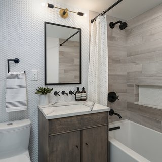 Interior design firm Eneia White Interiors established a modern twist on the classic penny round in this bathroom, pairing matte-black finishes with warm grays to create a clean and timeless aesthetic.