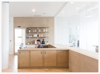 Wood warms up this otherwise all-white office for startup Eligible designed by Dani Arps. Fun, playful details like oversized, exposed white brackets to hold up shelving keep the space from feeling too serious while still being on-brand and design-forward.