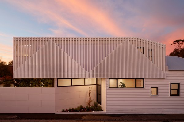 Inspired by the slopes and angles of the existing home's gabled roof and those of the Victorian homes in the area, the design team created a faceted, angular facade of vertical battens for the new extension.