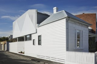 As an addition to a listed home in Melbourne, the local preservation regulations required the alteration be distinct from the historic home. This was done through both form and materiality.