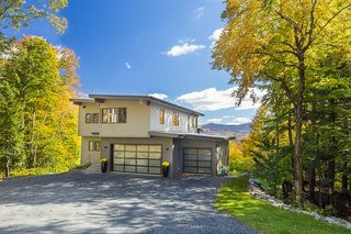 12 Modern Marvels in New England - Photo 3 of 12 - The Mad River Modern by Yankee Barn Homes is a 21st Century take on the Mid-Century Modern style. The home was built on a sloped site, but would work equally well on a level lot. An open floor plan and floor-to-ceiling windows allow for maximum natural light and integration with the outdoors. A neutral color palette emphasizes the natural warmth of the post and beam frame. The open living plan progresses seamlessly to the outdoors through over-size windows and doors. Built in the Green Mountains of Vermont by avid outdoor enthusiasts, the Mad River Modern allows complete engagement with the out-of-doors, even on a cold day when tucked snugly inside by a cozy fire!