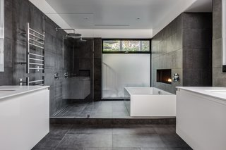 In this master bathroom, which is complete with a soaking tub, a linear fireplace, and floating vanities, the floor and walls are covered with large-format Italian porcelain tile from Emil Ceramica.