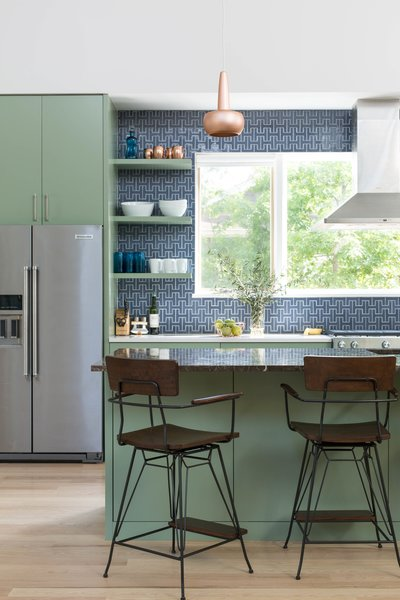 For the kitchen, the architect selected a recycled Fireclay Tile in Slate Blue and paired that with High Park paint from Benjamin Moore. Copper pendants from VITA accent the space. The vent hood is mounted in front of a large window, bringing in natural light and allowing for a view of the herb garden.