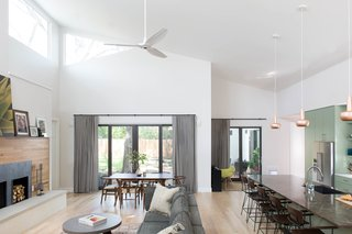 The open concept living/dining/kitchen has a large vaulted ceiling with rectangular and triangular clerestory windows that wash the space with tree-dappled natural light from high above.