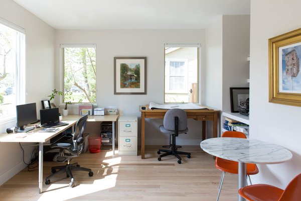 The architect's home office, situated in the front corner of the house, allows for ample natural light and views. The office has its own entrance and is attached to the powder bath, which can also be entered from the hallway near the living room.