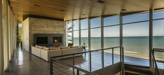Nestled between the sand dunes of Lake Michigan to the north and a steep wooded terrain to the south, the two-level home opens and connects to both environments. With the shifting sand dunes creating the topography of the site, the board-formed concrete base recedes into the rising woods while the all-glass living room and master suite above become a raised platform, or aerie, with views of both breathtaking landscapes.