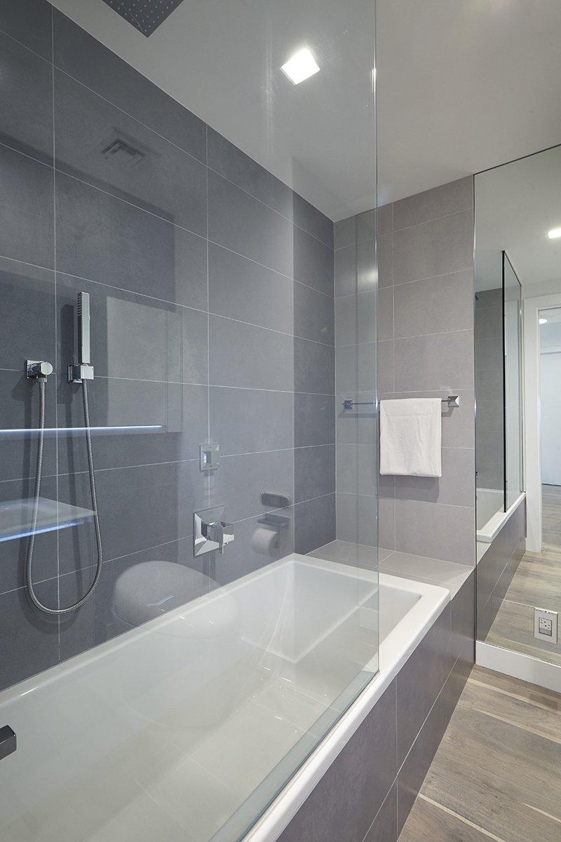 Bath, Medium Hardwood, Alcove, Corner, Soaking, Ceiling, and Porcelain Tile  Bath Corner Medium Hardwood Photos from White on White Apartment