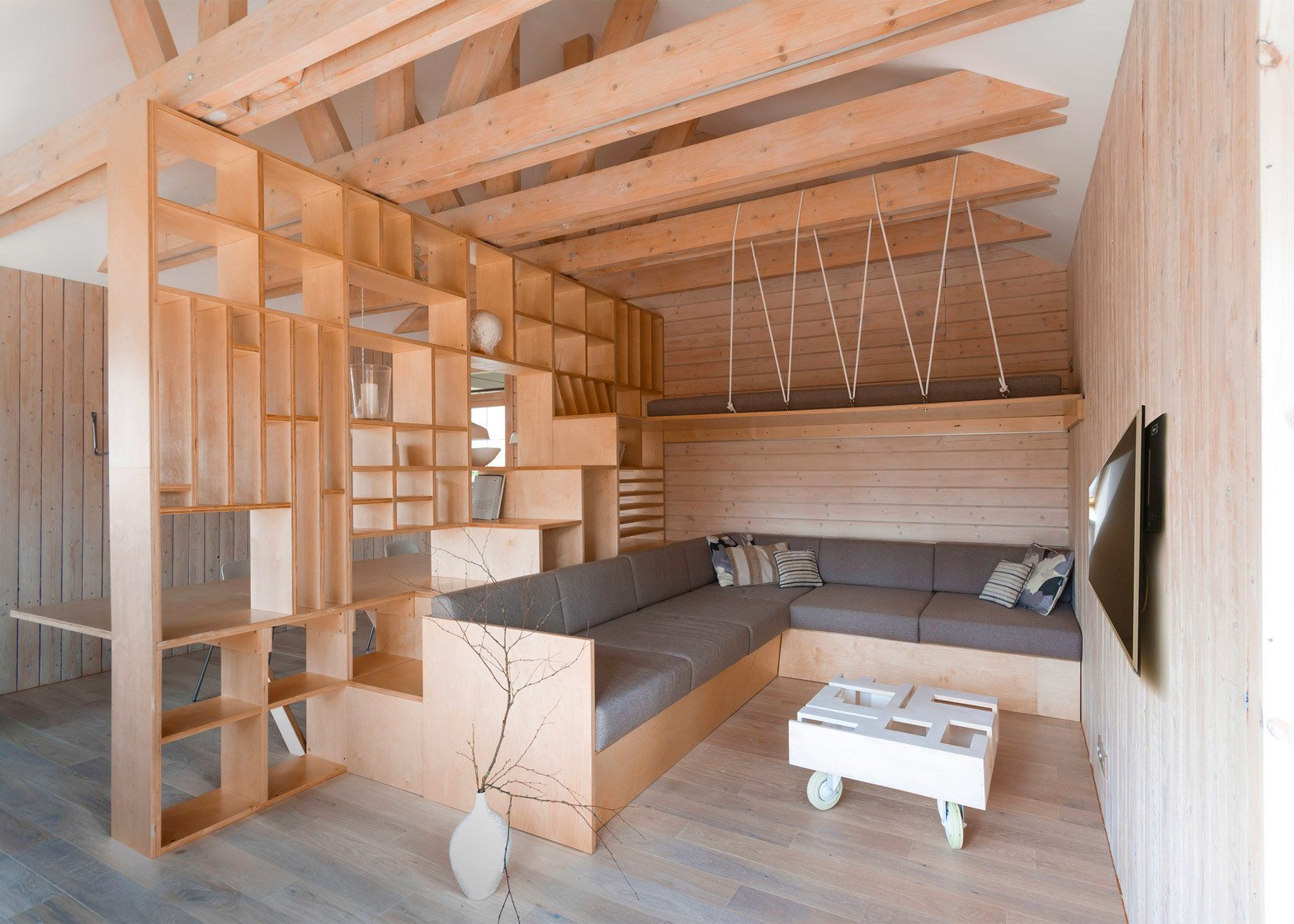 Russian-based studio Ruetemple conjured a plywood partition that  separates working and relaxation areas inside this artist's studio in Moscow, incorporating both furniture and shelves for tidying away art supplies. Tagged: Living Room.  Photo 7 of 11 in 10 Space-Saving Interiors For Multifunctional Living from Space-saving Interiors