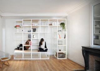 In the living room, modular wooden shelves and cabinets create areas that can be used as bookcases, seating, or as a climbing frame.