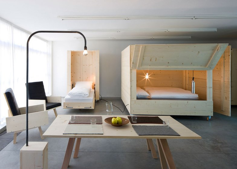 Living Room Named Atelierhouse, for contemporary art museum Museion as a temporary home for visiting artists and curators, Harry Thaler Studio employed wooden boxes on wheels fold open to reveal beds inside.    Photo 4 of 11 in 10 Space-Saving Interiors For Multifunctional Living from Space-saving Interiors