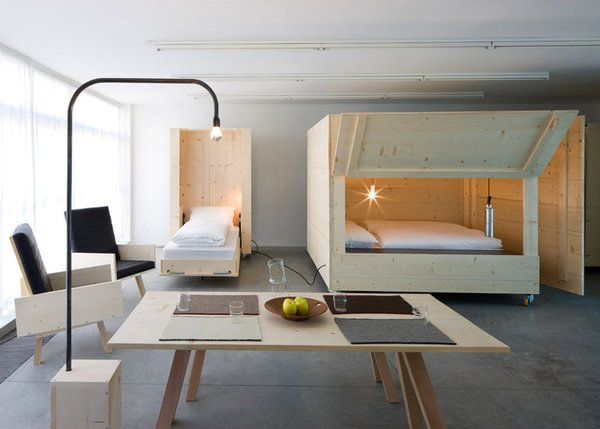Living Room Named Atelierhouse, for contemporary art museum Museion as a temporary home for visiting artists and curators, Harry Thaler Studio employed wooden boxes on wheels fold open to reveal beds inside.    Photo 4 of 11 in 10 Space-Saving Interiors For Multifunctional Living