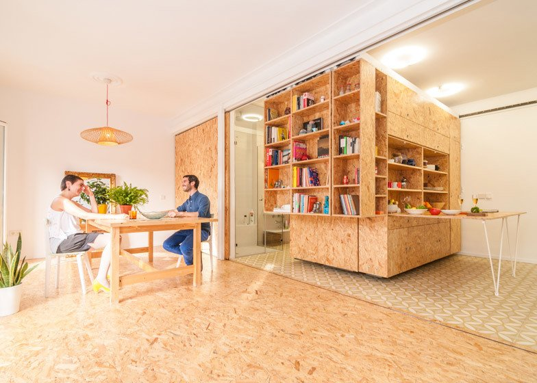 Moveable library-style shelving units slide from side to side to reveal and hide compartments that serve various functions in the Madrid apartment by PKMN Architectures. Tagged: Living Room.  Photo 5 of 11 in 10 Space-Saving Interiors For Multifunctional Living from Space-saving Interiors