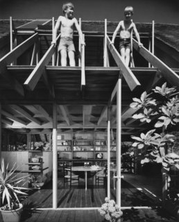 In this photo of the Diamond Street House taken by Julius Shulman, Brock Lyster (left) stands next to his brother on his father's roof truss.