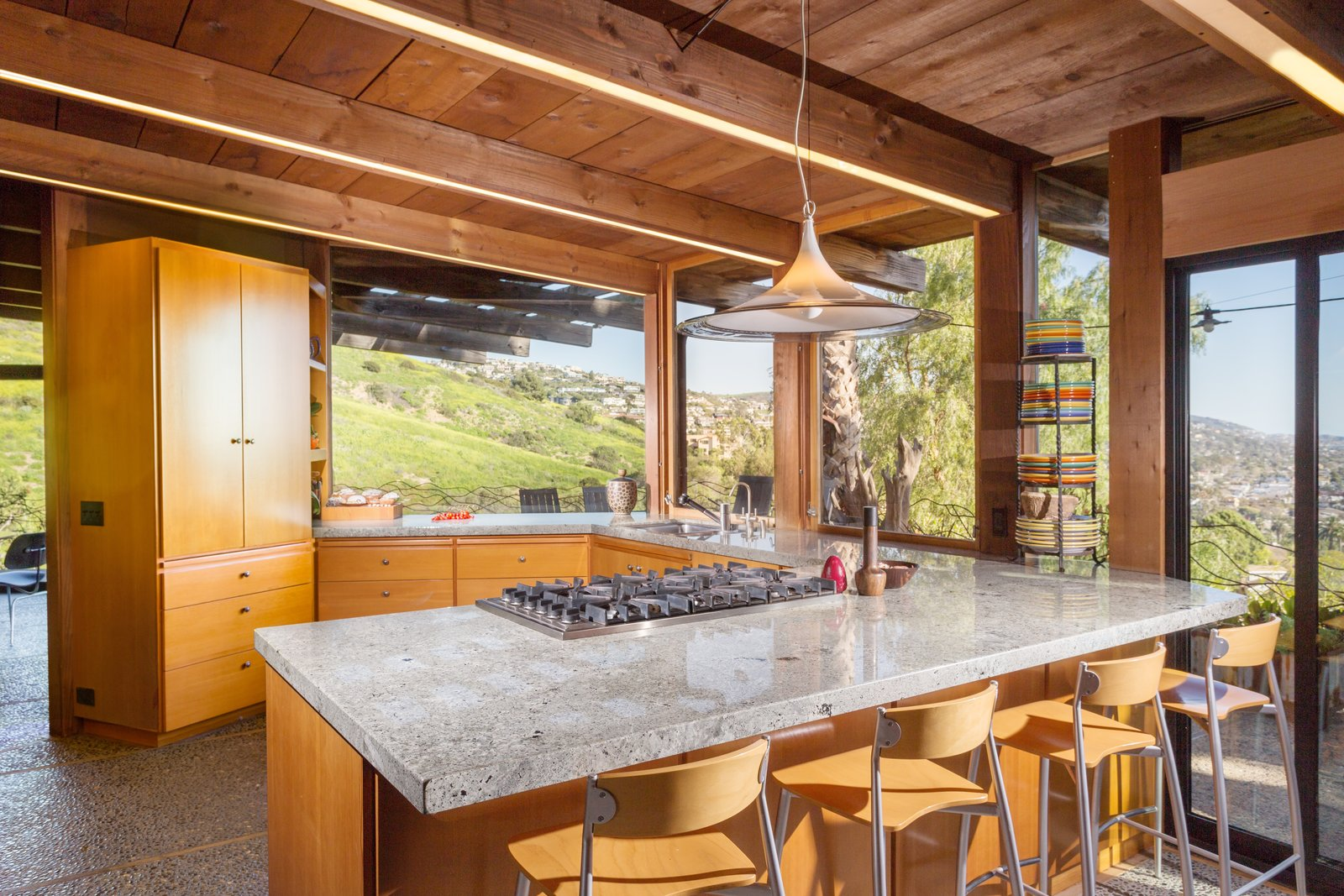 Kitchen, Granite Counter, Wood Cabinet, Range, Concrete Floor, and Pendant Lighting  Photo 6 of 13 in A 1974 Masterpiece Is Put on the Market by a Family Friend of the Late Julius Shulman