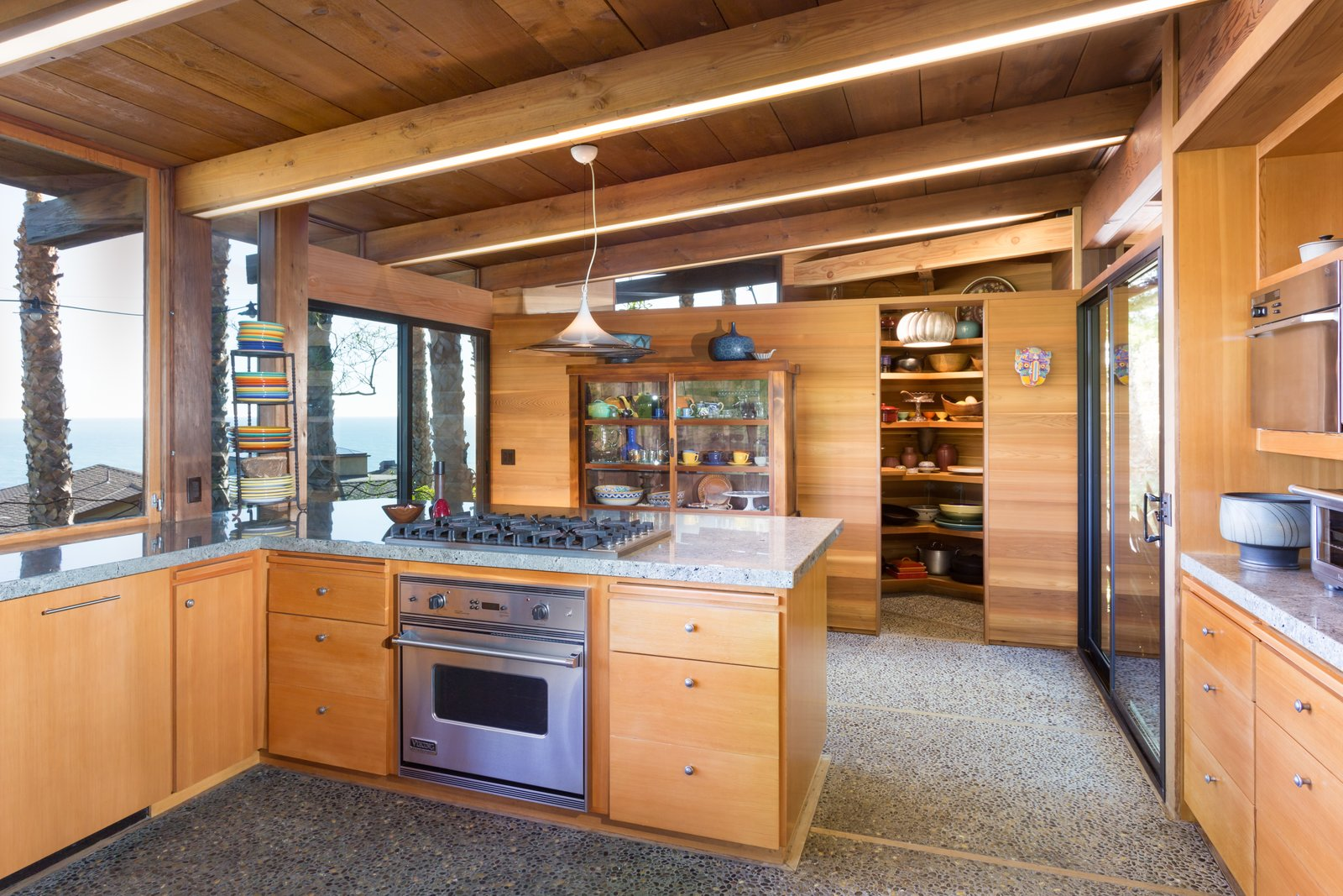 Kitchen, Range, Wood Cabinet, Granite Counter, Concrete Floor, and Pendant Lighting  Photo 11 of 13 in A 1974 Masterpiece Is Put on the Market by a Family Friend of the Late Julius Shulman