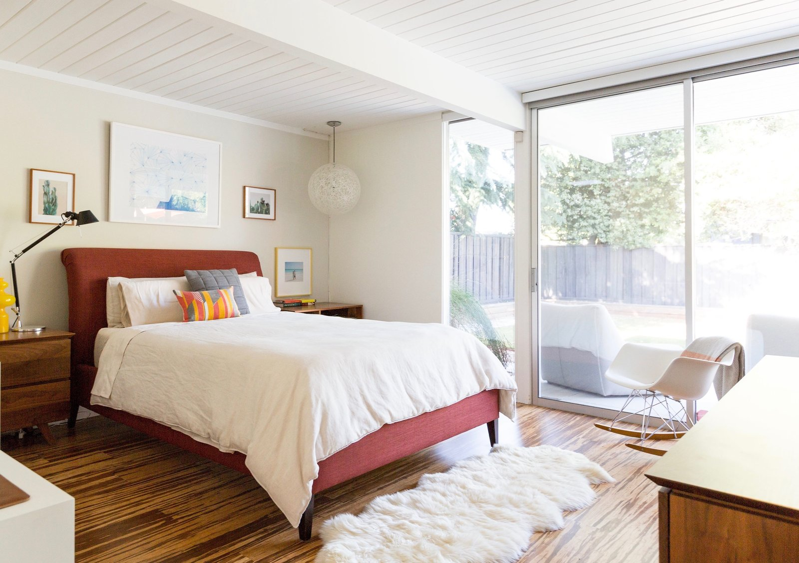 Bedroom, Bed, Night Stands, Pendant, Dresser, Rockers, Medium Hardwood, Table, Rug, and Lamps  Bedroom Medium Hardwood Pendant Rockers Photos from An Interior Designer Launches Her Career by Renovating Her Family's Midcentury Eichler
