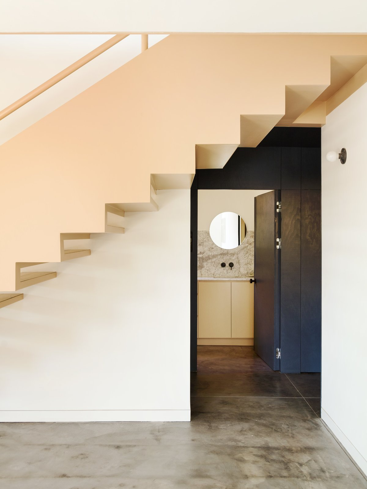 Hallway and Concrete Floor On a sloped plot in the Echo Park neighborhood of Los Angeles, an almost 100-year-old anonymous bungalow was rendered in pink, referencing the sun-kissed stucco that's so common in the region.  Mexico City-based architecture firm PRODUCTORA completely remodeled and renovated the home of graphic designer Jessica Fleischmann, daughter of Ernst Fleischmann, who led the Los Angeles Philharmonic and commissioned Frank Gehry to build the Walt Disney Concert Hall. Over the 15 years she lived in the home, she developed a strong connection to the neighborhood and the house itself, which inspired her to renovate it. With her strong affinity for design, she was thoroughly involved in the creative process, including selecting the particular colors that are interspersed throughout the renovation and extension of the house.  Photo 6 of 14 in Grids and Colors Inspire the Renovation of a Graphic Designer's Pink L.A. Bungalow