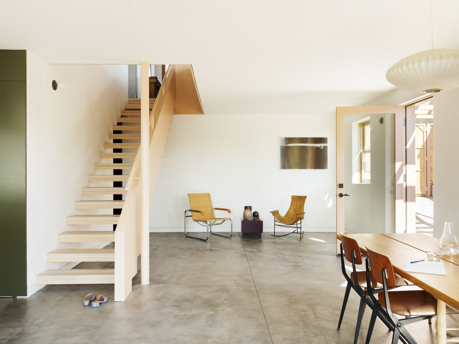 Chair, Concrete Floor, Wood Tread, Wood Railing, Living Room, End Tables, Pendant Lighting, and Table Lighting  Photo 4 of 14 in Grids and Colors Inspire the Renovation of a Graphic Designer's Pink L.A. Bungalow