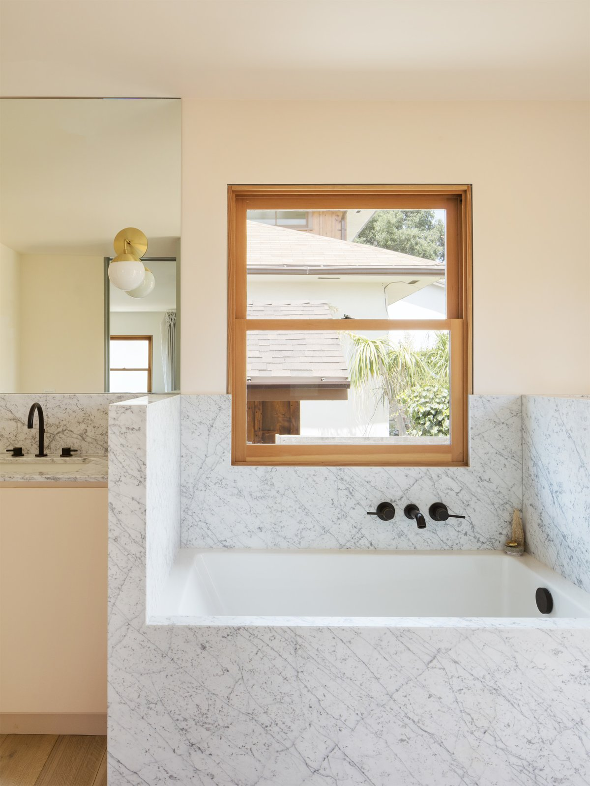 Bath Room, Marble Counter, Soaking Tub, Light Hardwood Floor, Undermount Sink, and Wall Lighting  Best Photos from Grids and Colors Inspire the Renovation of a Graphic Designer's Pink L.A. Bungalow