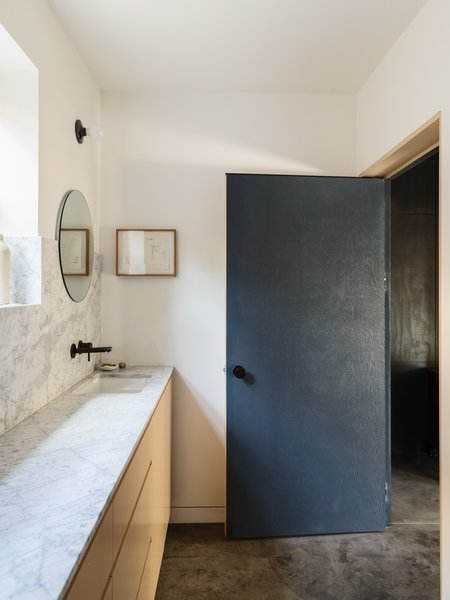 Bath Room, Marble Counter, Concrete Floor, Undermount Sink, and Wall Lighting  Photo 10 of 14 in Grids and Colors Inspire the Renovation of a Graphic Designer's Pink L.A. Bungalow