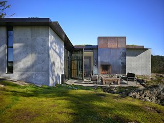 Throughout the house, the rock extrudes into the space, contrasting with the luxurious textures of the furnishings. Interior and exterior fireplace hearths are carved out of existing stone; leveled on top, they are otherwise left raw. A large pivoting steel and glass door opens for access to an outdoor terrace.