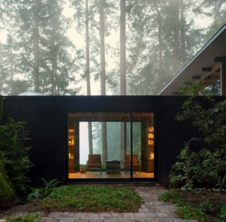 The cabin is intentionally subdued in color and texture, allowing it to recede into the woods and defer to the beauty of the landscape.