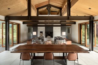 The double-sided fireplace separates the open-plan living, dining, and kitchen area from the library.