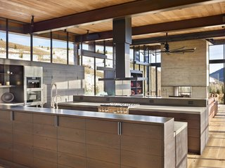"At this home in Sun Valley, the clients wanted a modern house that would feel authentic to the high desert mountain landscape, in a style dubbed ""mountain industrial."" Everything that touches the earth is stone and board-formed concrete, and everything that projects out is steel and glass, down to the kitchen island, which features two levels, an integrated sink, custom cabinetry, and polished nickel hardware."