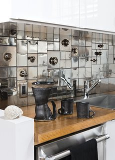 In kitchens that are looking for a more glam feeling, metallic or reflective tiles and materials can be a great idea. The slight changes in color of this metallic tile backsplash add visual interest and make for a consistent color palette with the stainless steel appliances.