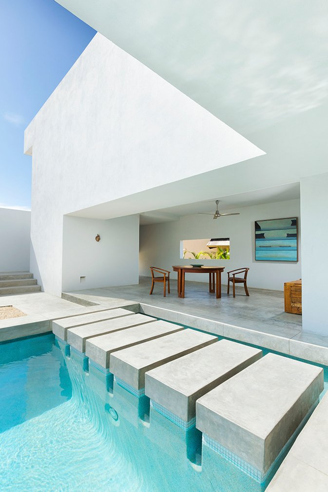 Outdoor, Concrete Patio, Porch, Deck, and Swimming Pools, Tubs, Shower Designed by Campos Leckie to invoke a pure, dream-like quality, this minimalist retreat is situated on a hill above Zippers Beach overlooking the Sea of Cortez. The bold geometric angles, stripped down interior, and whitewashed walls allow for maximum light and shadow play throughout the day. The home features a zen garden, central pool, and a rooftop patio with sweeping views of the ocean and mountains.  Photo 6 of 11 in 10 Modernist Beach Home Rentals to  Escape to This Summer