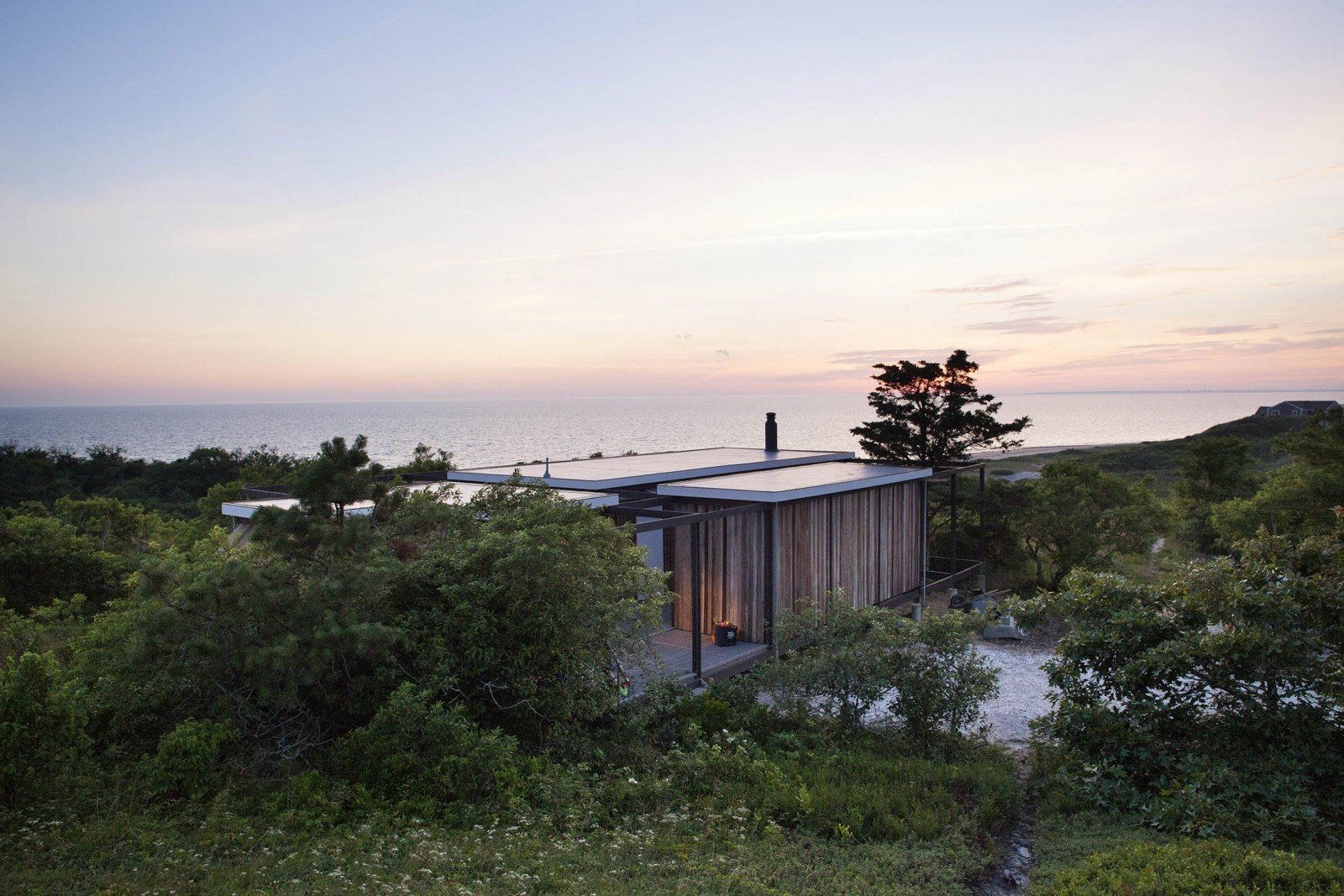 Outdoor, Slope, and Trees Originally designed by Jack Hall in the 1960s for Robert Hatch, an editor of The Nation and his wife, the  Photo 9 of 11 in 10 Modernist Beach Home Rentals to  Escape to This Summer