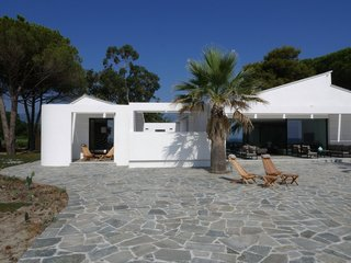 10 Modernist Beach Home Rentals to  Escape to This Summer - Photo 10 of 10 - Located steps from the beaches of Corsica, this striking modern beach house was designed by Paris-based architect Vincent Leprince, as a bright and bold reference to the sunshine-washed coastal surroundings. It features living room doors that open onto a terrace with panoramic views, and that leads directly to the beach. The home is tastefully decorated with contemporary furnishings and includes a heated spa with views of the island of Monte Cristo.