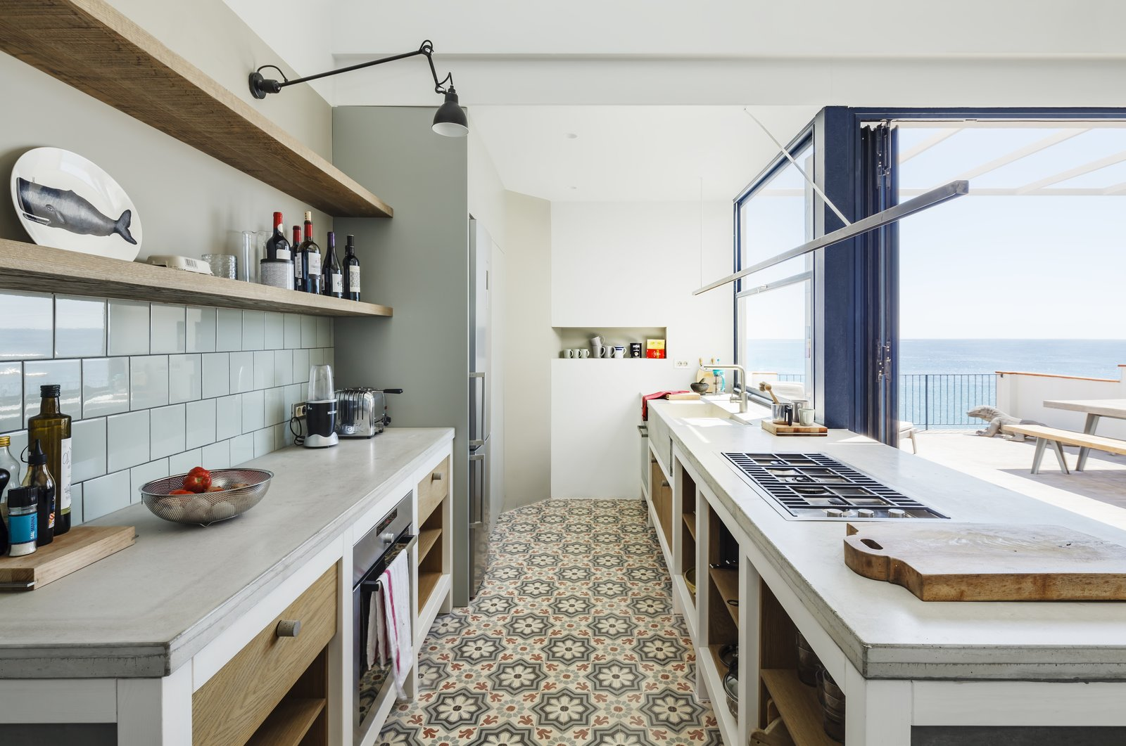 Kitchen, Concrete Counter, Ceramic Tile Floor, Refrigerator, Wall Oven, Porcelain Tile Backsplashe, Wall Lighting, Range, and Drop In Sink  Photo 8 of 16 in A Careful Renovation Brings New Life to a Family's Heritage Home on the Spanish Coast