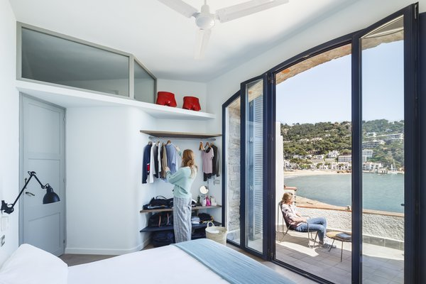 Tagged: Bedroom, Bed, Wall Lighting, Shelves, and Storage.  Es Garbi Beach House from A Careful Renovation Brings New Life to a Family's Heritage Home on the Spanish Coast